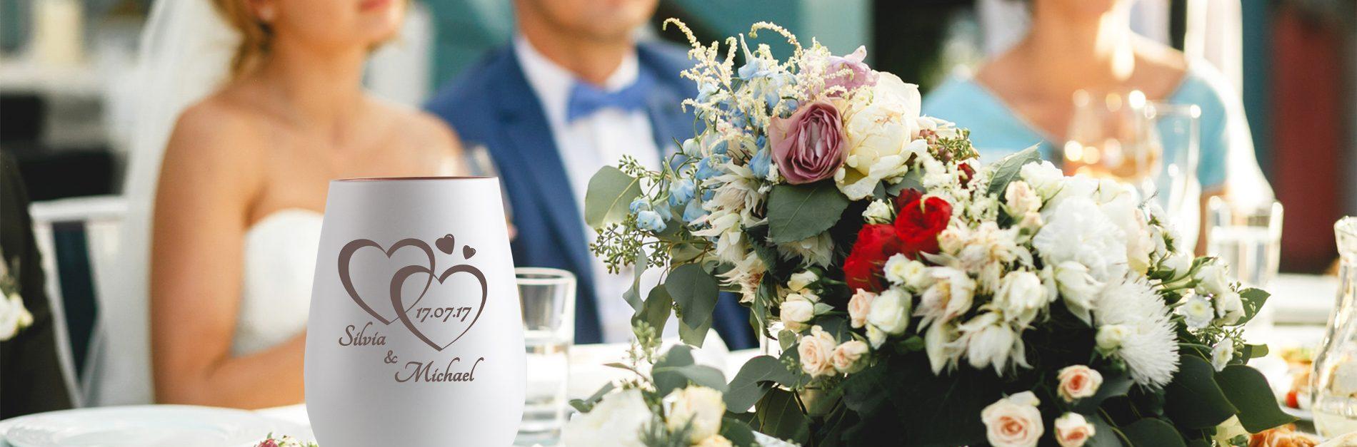 ein Brautpaar sitzt an einem festlich gedeckten Hochzeits-Tisch
